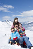 Portrait of happy family hugging on snowy mountain Stock Photography