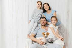 Portrait of happy family indoor. Handsome father holds dog, beau stock photography