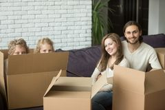 Happy family with kids and boxes on moving day, portrait. Portrait of happy family with kids on moving day, cute children son and daughter playing peeking from Stock Photos