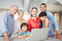 Portrait of happy family with laptop at home Stock Photography