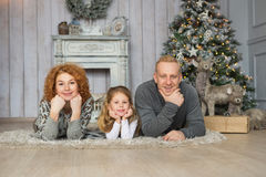 Portrait of happy family lie on a carpet near Christmas tree Royalty Free Stock Images