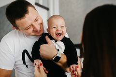 Portrait of a happy family with a little baby boy. Father is holding his son on his hands, while he is looking at his mother and smiling royalty free stock photography