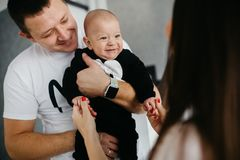 Portrait of a happy family with a little baby boy. Father is holding his son on his hands, while he is looking at his mother and smiling stock photography