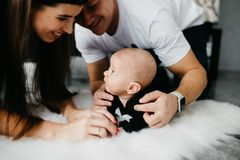Portrait of a happy family with a little baby boy. They are lying on the floor, embracing and looking at each other royalty free stock image