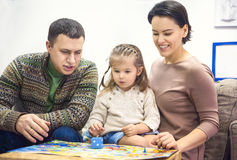 Portrait of happy family with little daughter playing table game Stock Photography