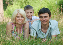 Portrait of happy family lying down on grass. Stock Photo