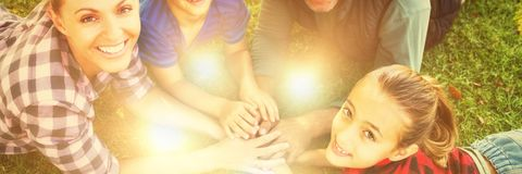 Happy family lying and putting their hands together in park. Portrait of happy family lying and putting their hands together in park royalty free stock photos