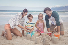 Portrait of happy family making sand castle Stock Images
