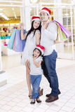 Portrait of happy family at mall. Joyful family posing and smiling at camera while carrying shopping bags in the mall Stock Images