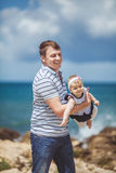 Portrait of a Happy family of man and child having fun by the blue sea in summertime Royalty Free Stock Images