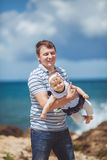 Portrait of a Happy family of man and child having fun by the blue sea in summertime Stock Photography