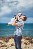 Portrait of a Happy family of man and child having fun by the blue sea in summertime Stock Image