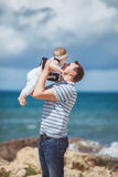 Portrait of a Happy family of man and child having fun by the blue sea in summertime Stock Photos