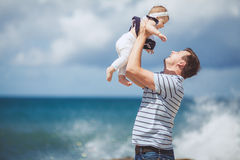 Portrait of a Happy family of man and child having fun by the blue sea in summertime Royalty Free Stock Photography