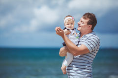 Portrait of a Happy family of man and child having fun by the blue sea in summertime Royalty Free Stock Photo