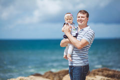 Portrait of a Happy family of man and child having fun by the blue sea in summertime Royalty Free Stock Photos