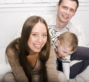 Portrait of happy family, mom and dad playing with their son in bed. Close up stock photography