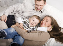 Portrait of happy family, mom and dad playing with their son in bed Stock Photo