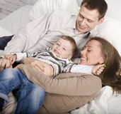 Portrait of happy family, mom and dad playing with their son in bed. Close up Stock Images