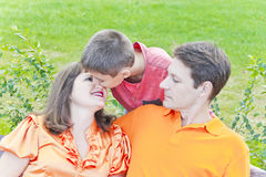 Portrait of happy family with mother father and son. Happy family son kissing pregnant mother in summer time Stock Photos