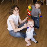 Portrait of happy family, mother playing with sons Stock Photography