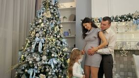 Portrait of a happy family near a Christmas tree. A little girl strokes her pregnant mom`s belly standing near the Christmas tree stock video