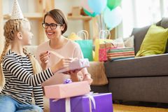 Opening Birthday Gifts with Mom. Portrait of happy family opening presents at home after Birthday party, copy space stock photography