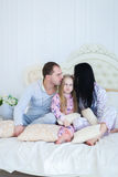 Portrait of happy family in pajamas smiling and looking at camer. Child with mom and dad sit on bed, smiling and looking at camera. Young happy couple together royalty free stock images