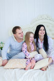 Portrait of happy family in pajamas smiling and looking at camer. Child with mom and dad sit on bed, smiling and looking at camera. Young happy couple together stock photography
