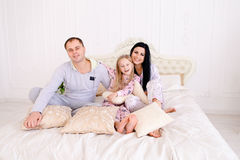 Portrait of happy family in pajamas smiling and looking at camer. Child with mom and dad sit on bed, smiling and looking at camera. Young happy couple together stock images