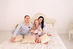Portrait of happy family in pajamas smiling and looking at camer. Child with mom and dad sit on bed, smiling and looking at camera. Young happy couple together royalty free stock image