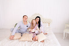 Portrait of happy family in pajamas smiling and looking at camer. Child with mom and dad sit on bed, smiling and looking at camera. Young happy couple together stock image
