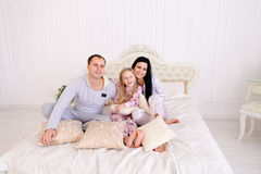 Portrait of happy family in pajamas smiling and looking at camer. Child with mom and dad sit on bed, smiling and looking at camera. Young happy couple together stock photo
