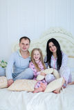 Portrait of happy family in pajamas smiling and looking at camer. Child with mom and dad sit on bed, smiling and looking at camera. Young happy couple together royalty free stock photography