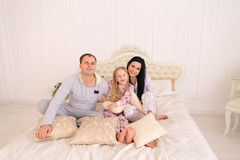 Portrait of happy family in pajamas smiling and looking at camer. Child with mom and dad sit on bed, smiling and looking at camera. Young happy couple together royalty free stock photos