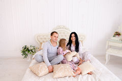 Portrait happy family in pajamas smiling and looking at camera i. Child, mom and dad sit on bed, smiling and looking at camera. Young happy couple together royalty free stock photography
