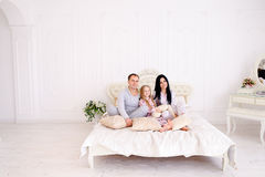 Portrait happy family in pajamas smiling and looking at camera i. Child, mom and dad sit on bed, smiling and looking at camera. Young happy couple together royalty free stock photos