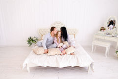 Portrait happy family in pajamas smiling and looking at camera i. Child, mom and dad sit on bed, smiling and looking at camera. Young happy couple together stock photo