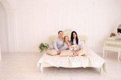 Portrait happy family in pajamas smiling and looking at camera i. Child, mom and dad sit on bed, smiling and looking at camera. Young happy couple together stock image