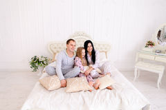 Portrait happy family in pajamas smiling and looking at camera i. Child, mom and dad sit on bed, smiling and looking at camera. Young happy couple together royalty free stock image