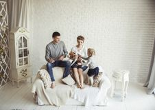 Portrait of happy family with pet dog on sofa in living room Royalty Free Stock Images