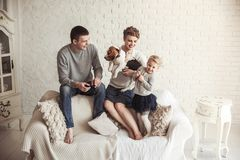 Portrait of happy family with pet dog on sofa in living room. Happy parents,five year old daughter with a pet dog sitting on the couch in the living room Stock Photos