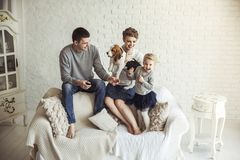 Portrait of happy family with pet dog on sofa in living room. Happy parents,five year old daughter with a pet dog sitting on the couch in the living room Stock Photography