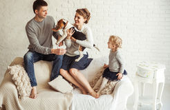 Portrait of happy family with pet dog on sofa in living room Royalty Free Stock Photos