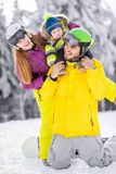 Happy family during the winter vacations. Portrait of a happy family playing with baby boy during the winter vacations on the beautiful mountains with snow royalty free stock image