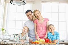 Portrait of happy family preparing food in kitchen Royalty Free Stock Photos