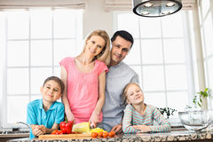 Portrait of happy family preparing food in kitchen Royalty Free Stock Images