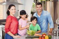 Portrait of happy family preparing salad Royalty Free Stock Photo