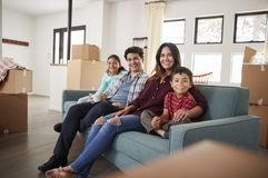 Portrait Of Happy Family Resting On Sofa Surrounded By Boxes In New Home On Moving Day stock photos
