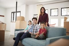 Portrait Of Happy Family Resting On Sofa Surrounded By Boxes In New Home On Moving Day royalty free stock image